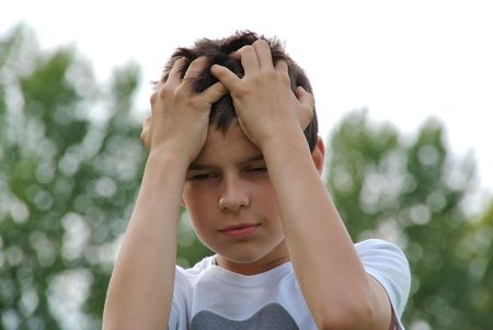 embarassment: A young kid looks angry or disappointed, holding two hands to his forehead