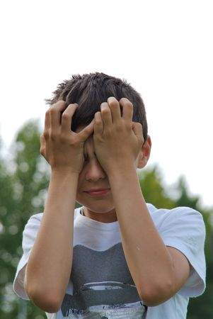 embarassment: A young kid is crying, holding two hands to his forehead
