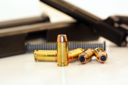 disassembled: Forty caliber bullet with a disassembled gun in the background Stock Photo