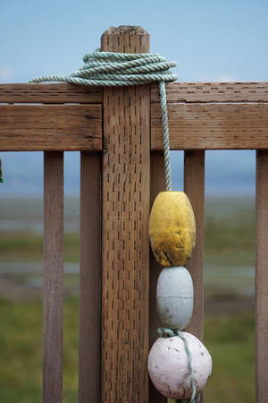 Boat buoys tied to fence Stock Photo
