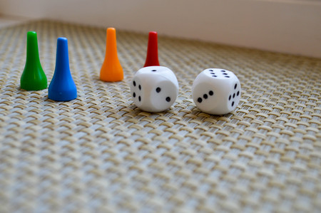 White dice and four figures for table games. Stock Photo