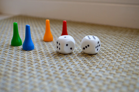 White dice and four chips for board games.
