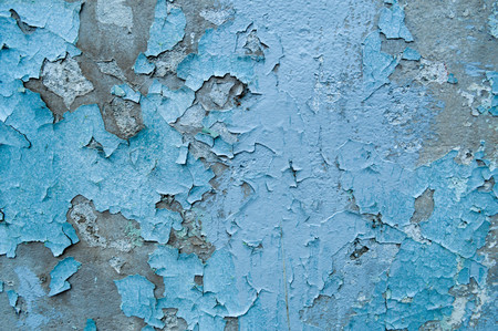 Old, blue, exfoliated, peeling paint on the concrete wall. The background. Texture.