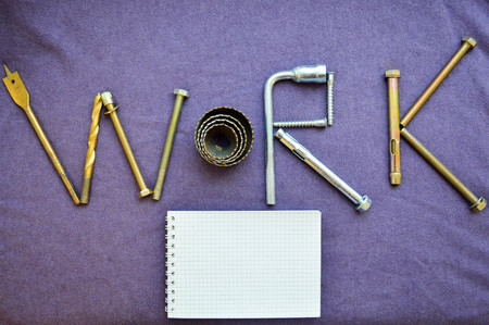 The inscription work is written by metal anchor bolts, screws, svermami, wrenches. work made up of objects. Word work made up by a metalwork tool and notepad.