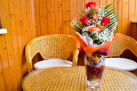 Red and yellow roses in a bouquet with interspersed white flowers on a table next to chairs made of straw. 写真素材