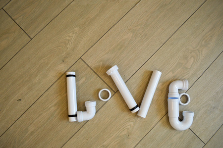 The word love is laid out of plumbing, plumbing white plastic pipes, fittings, flanges and gaskets on the background of beige boards. The text of the pipes. Inscription made of plastic pipes. Stock Photo