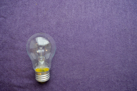 A round, ordinary, non-economical incandescent bulb with a transparent socle background of purple cloth. Stock Photo