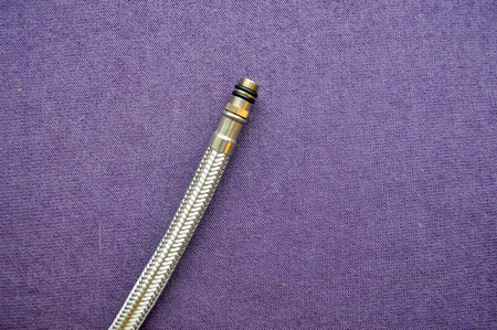 Threaded tap, reinforced, silver hose on a purple background. Plumbing fixture. A nut on the hose for a faucet.