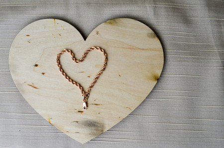 A heart made of a female gold chain on a beautiful, vintage, homemade, wooden heart to Valentines Day against a background of beige fabric. Stock Photo