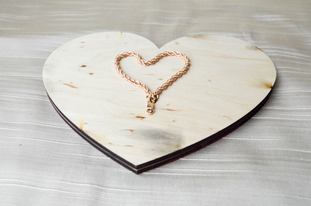 A heart made of a female gold bracelet on a beautiful, vintage, homemade, wooden heart to Valentines Day against a beige fabric background.