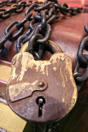 A huge old brown lock tied with thick, strong metal chains on a wooden background.