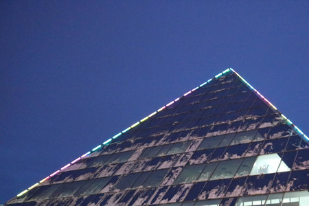 The corner of a triangular, glass, office, modern building with luminous windows, a skyscraper covered with snow at night against a blue sky in winter.
