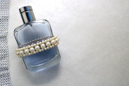 Blue beautiful glass transparent fashionable glamorous bottle of cologne, perfume with white gems and a place for a simple text on a light white background. Imagens