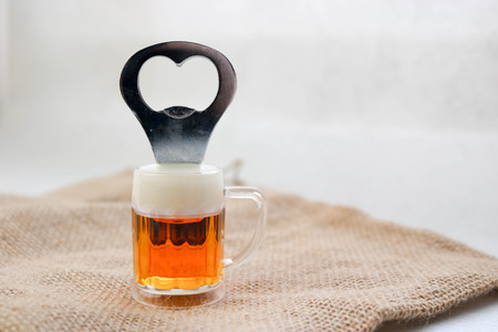 A yellow bottle opener in the form of a glass of beer with white foam against the texture of a brown old canvas linen natural cloth with a coarse perpendicular interlacing of the fibers of the fabric.