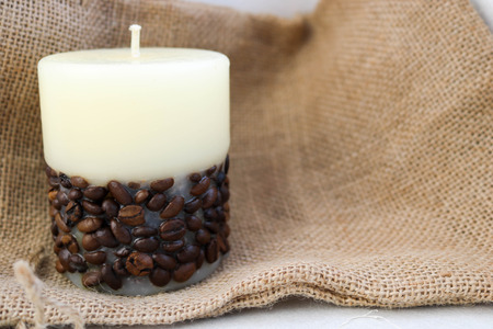 Wax beautiful light beige candle with unflavored wick from below decorated with coffee beans on the background of old brown canvas fabric.