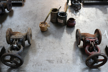 Two metal old latches, pipe fittings, cans with graphite grease, solidol on a large iron table in the factory, shop. Concept industry, work at the plant, refining equipment.
