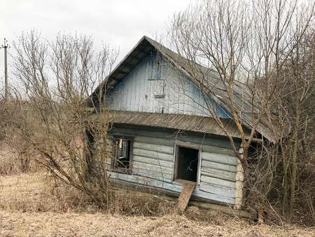 Old blue old dilapidated wooden abandoned ruined blue village house of beams with broken windows in the wilderness
