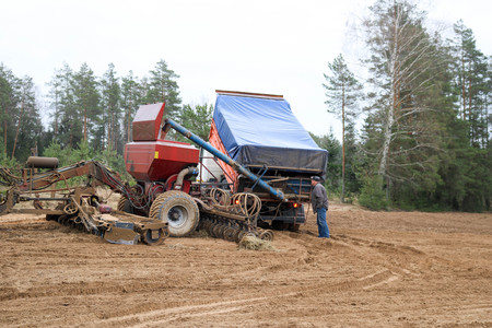 Sowing unit, combine harvester, seeder and lorry, dumper and worker on the field. Stock Photo