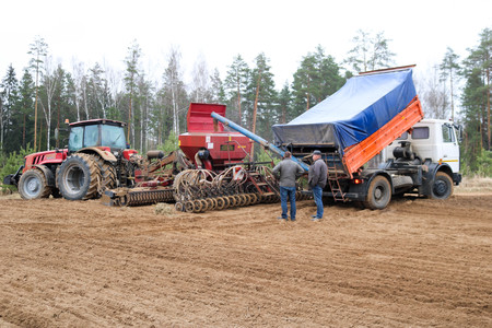 Sowing unit, combine harvester, seeder and lorry, dumper and workers on the field. Editorial