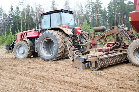 A tractor with a connected sowing unit, a combine, a drill with large wheels plows the field, sows grain, performs agrarian and farm work.