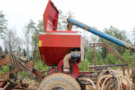 The grain falls into a large seeding unit, a combine with large wheels for plowing the land, a device for sowing grain crops, performing agrarian, agricultural, farming, field work.