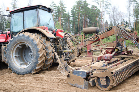 A powerful red tractor with a connected seeding unit, a combine, a drill with large wheels, travels across the field, sows grain crops, performs agrarian and farm work against the background of trees.