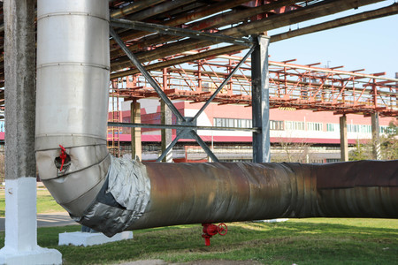 Pipeline estocada, large pipe with steam in insulation made of glass wool with red ventrals, fittings, valves, drainage with blue beams in oil refinery, petrochemical, chemical plant.