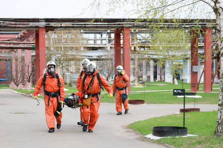 Four professional firefighter firefighters in orange protective fireproof suits, white helmets and gas masks carry the injured person on stretchers from the danger zone in the oil refinery