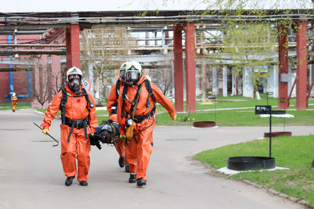 Three professional firefighter firefighters in orange protective fireproof suits, white helmets and gas masks carry the injured person on stretchers from the danger zone at the chemical plant