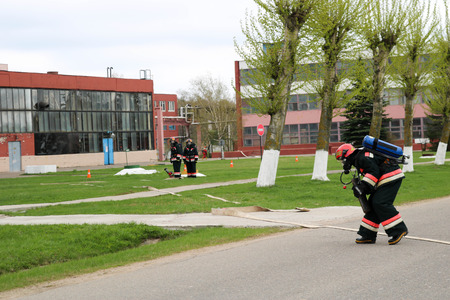 Professional firefighters, rescuers in protective fireproof suits, helmets and gas masks with oxygen bottles are prepared to rescue people from danger with a fire hose, a hose.