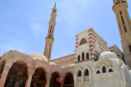 Moslem Islamic mosque of white brick for the collection of Muslims for general prayer, a liturgical architectural structure with arches, tall towers, domes and spiers against the blue sky