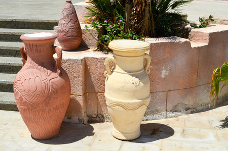 Three large stone, clay old ancient vintage burnt carved heavy jugs, vases with patterns on the stone floor against the backdrop of a stone staircase. Imagens