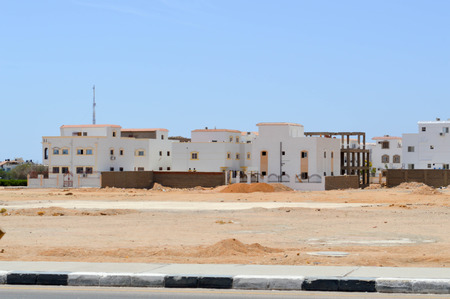 White Arabian rectangular houses in the desert with windows against the background of yellow sand and blue sky in Egypt and black and white bardry.
