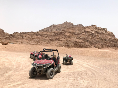 A lot of four-wheeled multicolored powerful fast off-road four-wheel drive buggies, cars, SUVs in the sandy hot desert on the sand in the parking lot against the background of high mountains. Standard-Bild - 104635259