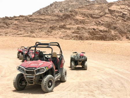 A lot of four-wheeled multicolored powerful fast off-road four-wheel drive  buggies, cars, SUVs in the sandy hot desert on the sand in the parking lot against the background of high mountains.