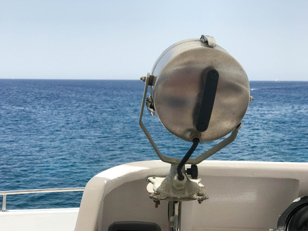 The searchlight is a silver metallic m of a powerful lamp mounted on a ship on the background of the sea, ocean, water. Stock Photo - 104828791
