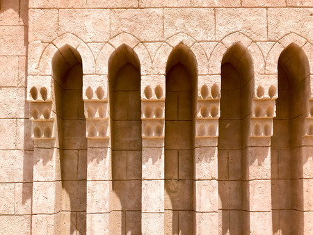 Texture of the old ancient yellow stone strong wall with arches in patterns and columns in an Arab Muslim Islamic warm tropical country in the desert. The background.