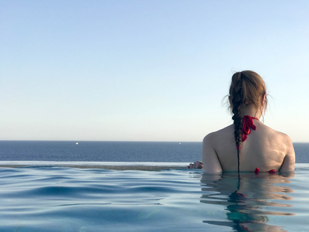A beautiful slender girl with her back in a red swimsuit swims, bathes the blue water of a luxurious infinity pool merging with the horizon on the background of the sea in a tropical warm sea resort. Stock Photo