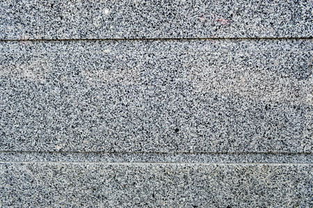 The texture of the stone wall is solid smooth of granite crumbs of two-color black and white with two horizontal stripes, lines. The background.