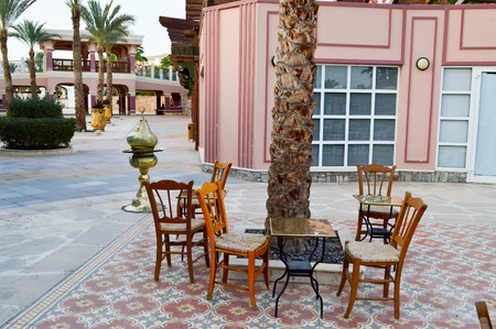 Open cafe hookah with tables and palm trees in a warm Arab Islamic Islamic country of tropical exotic under the open sky.