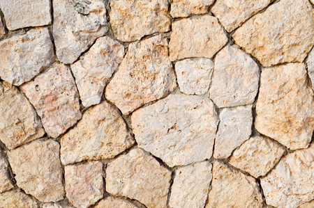 Texture of a stone wall, roads from stones, bricks, cobblestones, tiles with sandy seams of gray ancient natural old yellow with sharp edges