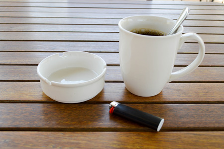 A white ceramic cup with a morning refreshing hot coffee with tea drink and tea shiny teaspoon and an empty ashtray with a black cigarette lighter stands on a wooden table in a cafe.
