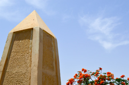 A large pointed obelisk made of yellow stone in Egypt against a blue sky and red flowers.