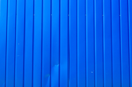 Texture of the blue vertical boards with the seams of the metal profile of the tin. The background.