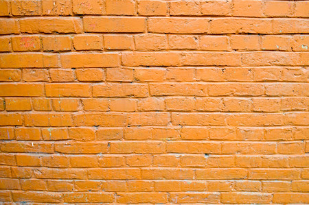 Texture of brick orange painted brown paint old brick wall with seams. The background.