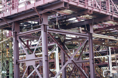 A large iron metal piping trestle with pipes and electric wires and equipment at the petrochemical refinery industrial refinery.
