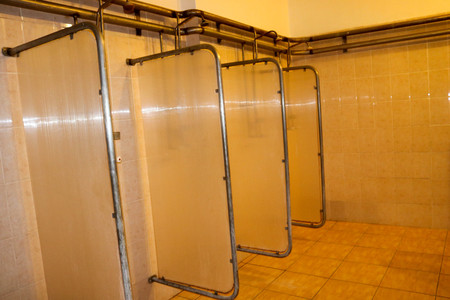 Shower cabins in the dressing rooms of workers at the industrial plant.