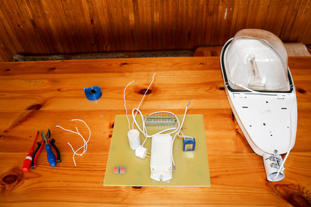 A large white disassembled street lamp with an electrical circuit with wires and spare parts, installation equipment, pliers, blue electrical tape, screwdrivers on the table. Standard-Bild