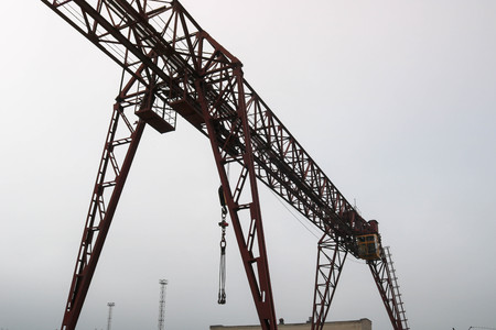 Industrial iron large metal gantry crane with a hook mounted on the supports for lifting and carrying heavy cargo, moving along the rails at the factory. The crane is of bridge type. Banque d'images