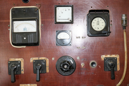 Large brown retro vintage electric shield with devices with arrows and scales, buttons and toggle switches, switches. Electrical equipment. Stock Photo